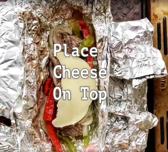 Cooked, sliced steak with cooked red and green peppers with a half slice of provolone cheese all in a foil packet with the words, place cheese on top to describe the photo across the middle.