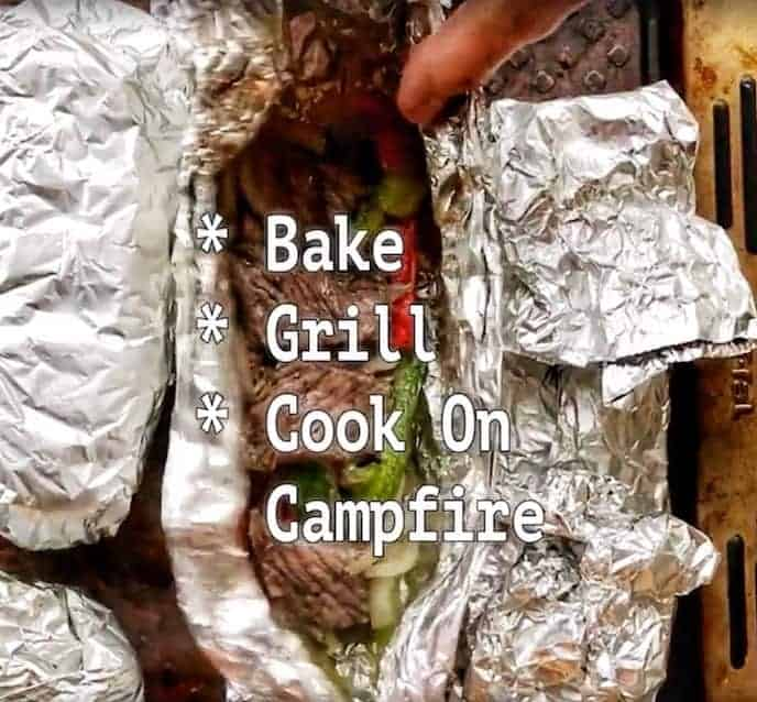 cooked sliced steak, red and green peppers and onions in a foil packet on a baking sheet with the words bake, grill, or cook on campfire across the front of the photo