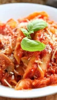 Chicken pasta with red sauce and mushrooms shown in a white bowl with fresh basil garnish and a fork.
