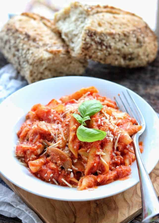 kid friendly crock pot meals showing crockpot chicken pasta in a white bowl with fork and a loaf of crusty bread in the background.