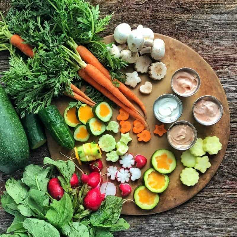 fresh vegetables including carrots, zucchini, and radishes. Veggie shapes with cheese inside and 4 small metal containers of dip all displayed on a pizza stone on a wood surface