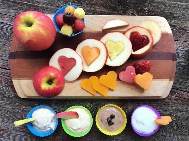 apples sliced in circles with hearts cut out of the middle. The hearts are filled in with heart shaped watermelon, and cantelope place on a wooden board with 4 fruit dips in silicone containers lined up in front