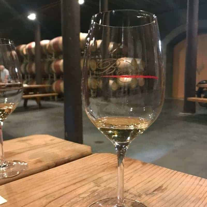 A glass of wine sitting on top of a wooden table