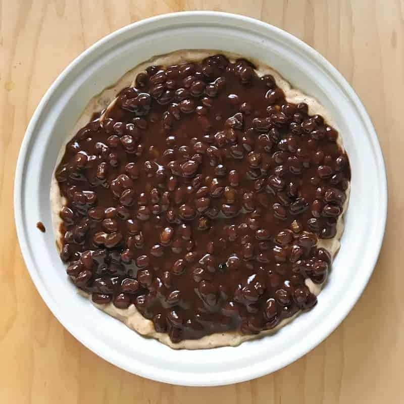 Seven layer bean dip recipe: the second layer of the recipe is black beans shown in a white pie pan.