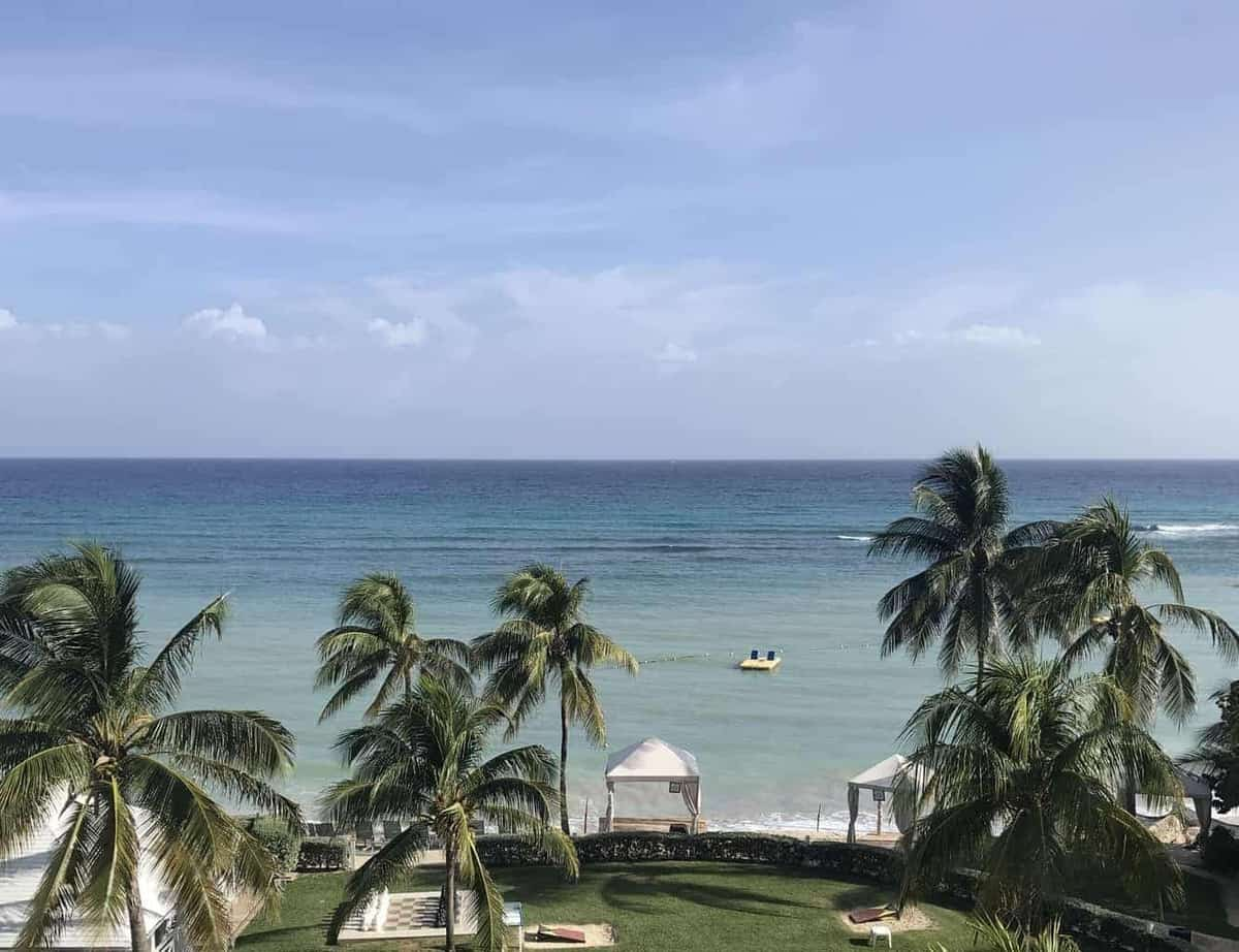 all inclusive resorts in montego bay jamaica showing the view from an ocean front room at Hilton Rose Hall Jamaica, showing the ocean and palm trees overlooking some large outdoor board games