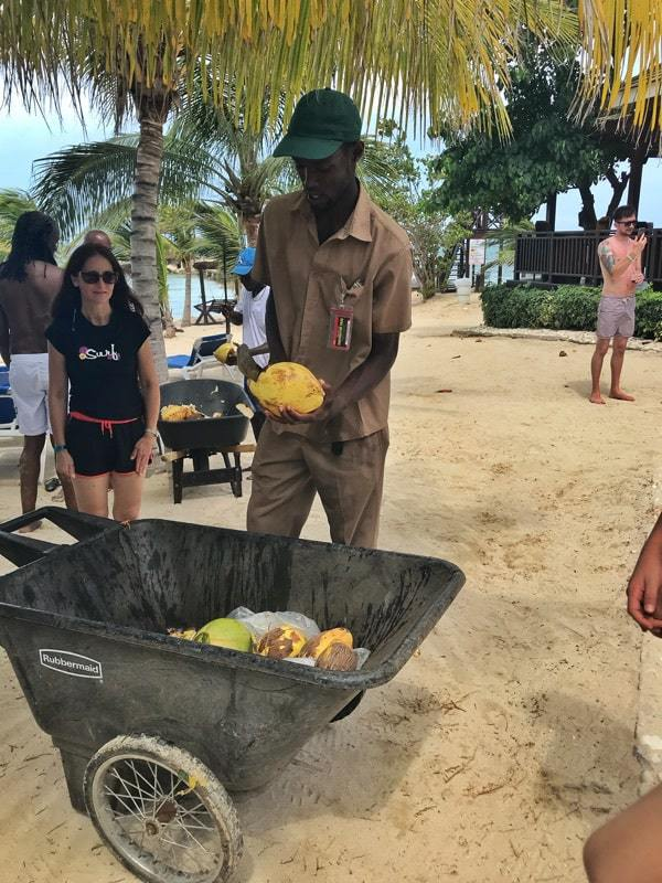 A man with a wheel barrow of coconuts slicing them open with a machete for guests.