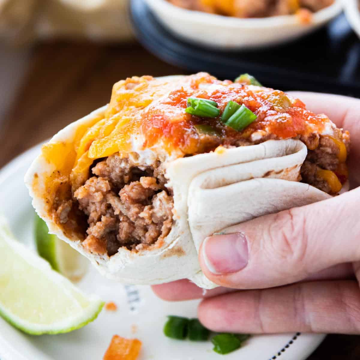 Baked Taco Cups showing a hand holding a cooked taco cup with toppings.