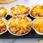A 6 muffin tin with taco cups filed with meat and cheese after baking.