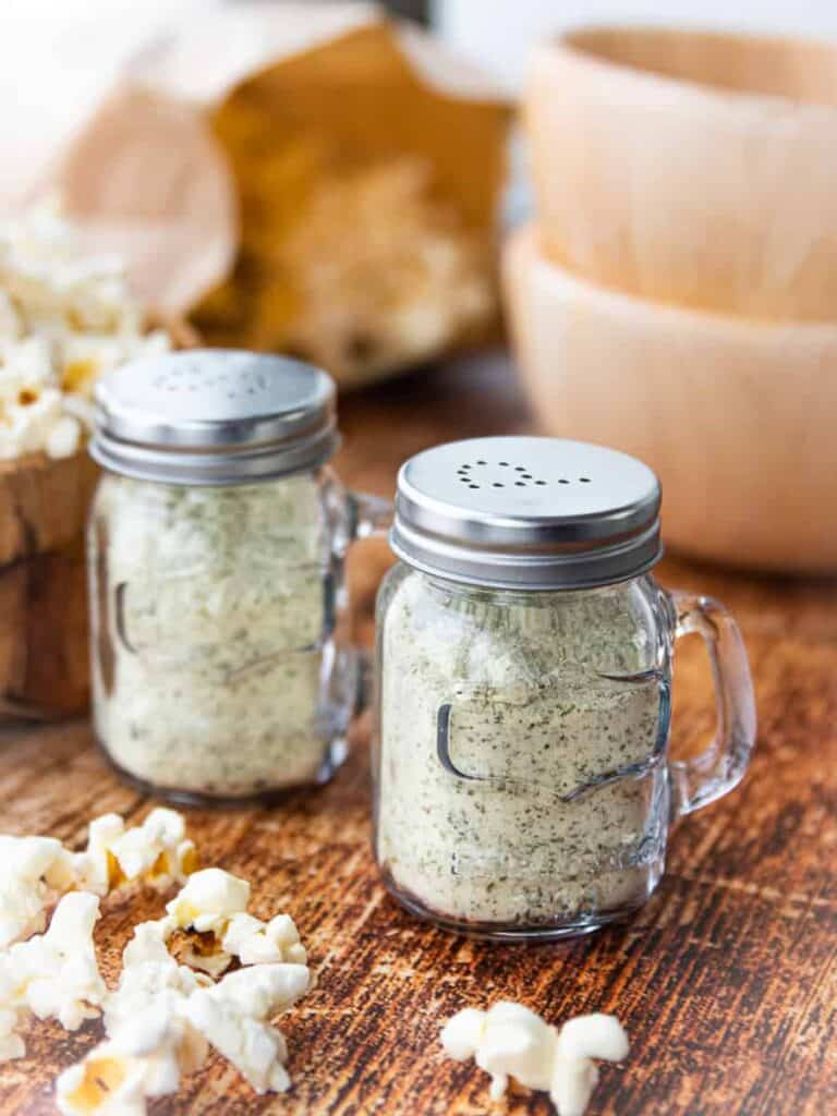 Ranch popcorn seasoning is shown in 2 glass containers on a wooden surface with 2 wooden bowls and popped popcorn in the background.