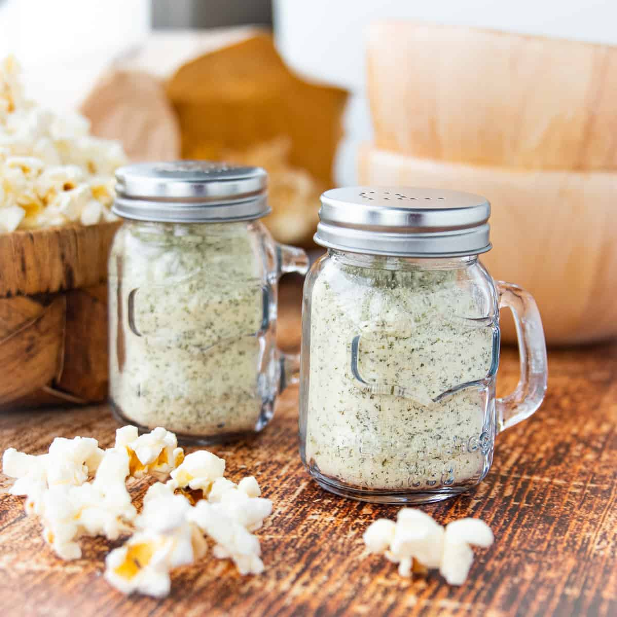 Two shakers of ranch popcorn seasoning surrounded by popped popcorn on a wooden surface.