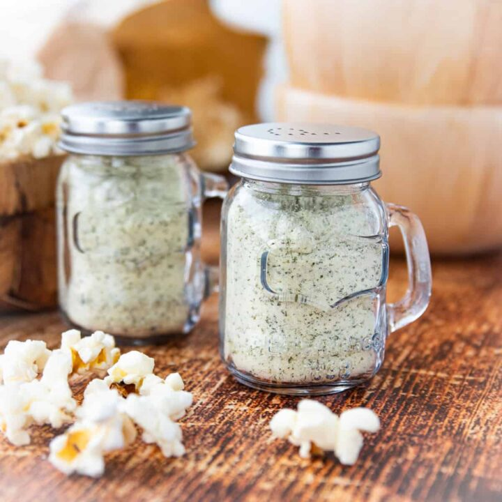 two shakers of ranch popcorn seasoning on a table with popcorn.