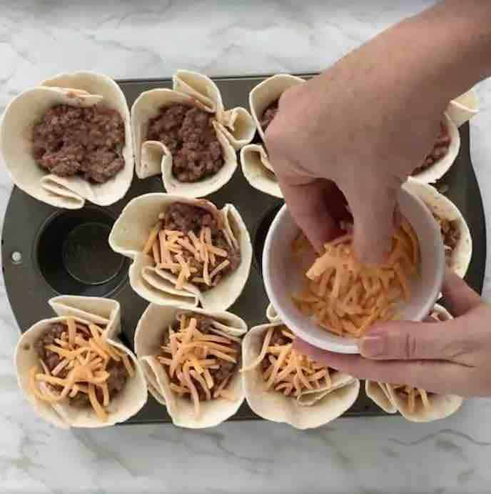 Baked taco cups in a muffin tin, filled with beef mixture and a hand is sprinkling shredded cheddar cheese on top. There is a white marble background.