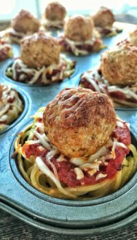 spaghetti and marinara sauce with meatballs in a 12 cup muffin tin.
