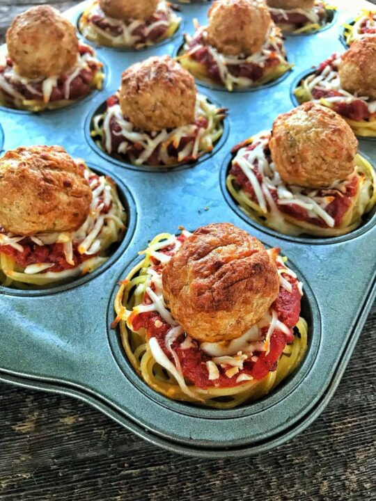 Spaghetti & Meatball Cups in a muffin tin filled with spaghetti, spaghetti sauce, cheese and a meatball on top of a black surface.