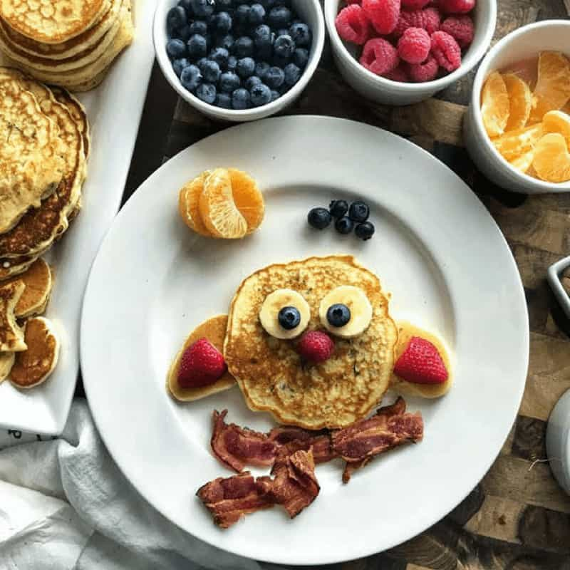 pancake recipe for kids showing an owl made from pancakes, bananas, strawberries, and blueberries along with bacon on a white plate with berries in the background.