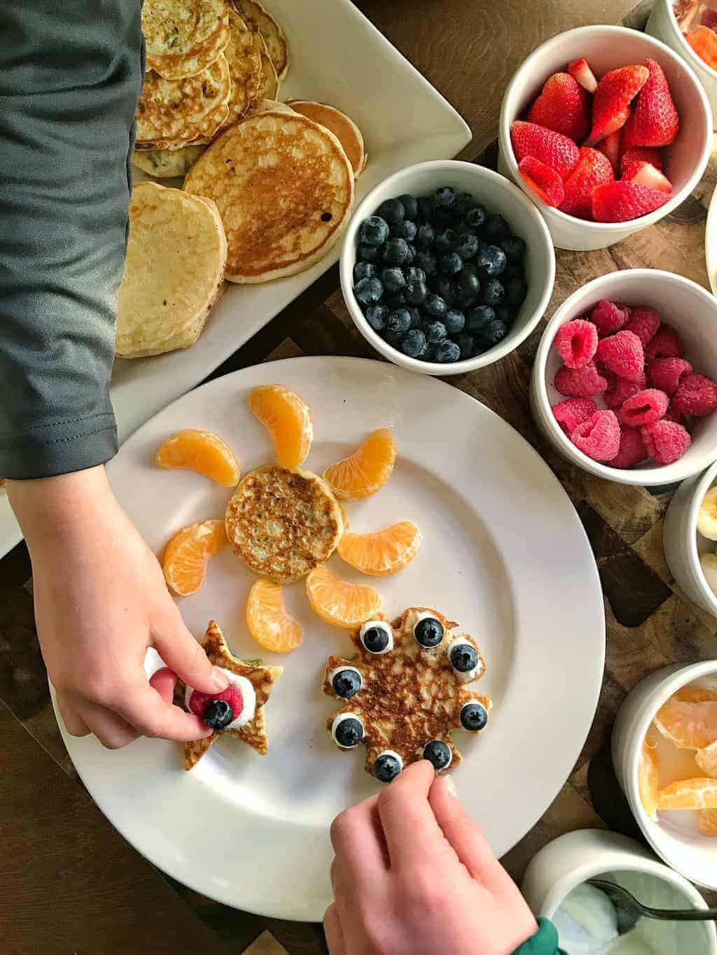 Fruit Pancakes, an easy recipe for kids showing hands decorating pancakes on a white plate with fruit.