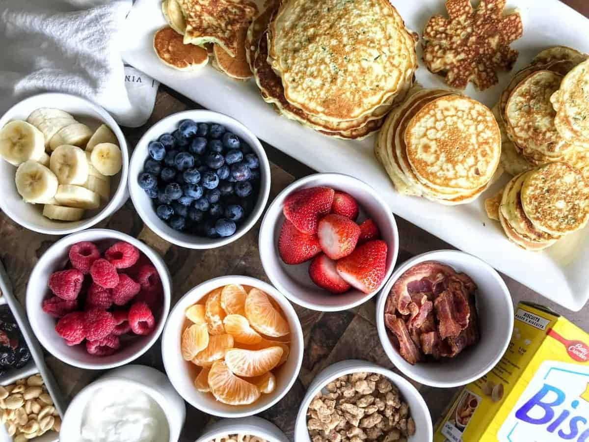 Fruit Pancakes, a bisquick recipe showing small white bowls with fruit and a platter of different sizes of pancakes, some bacon and sausage and Greek Yogurt.