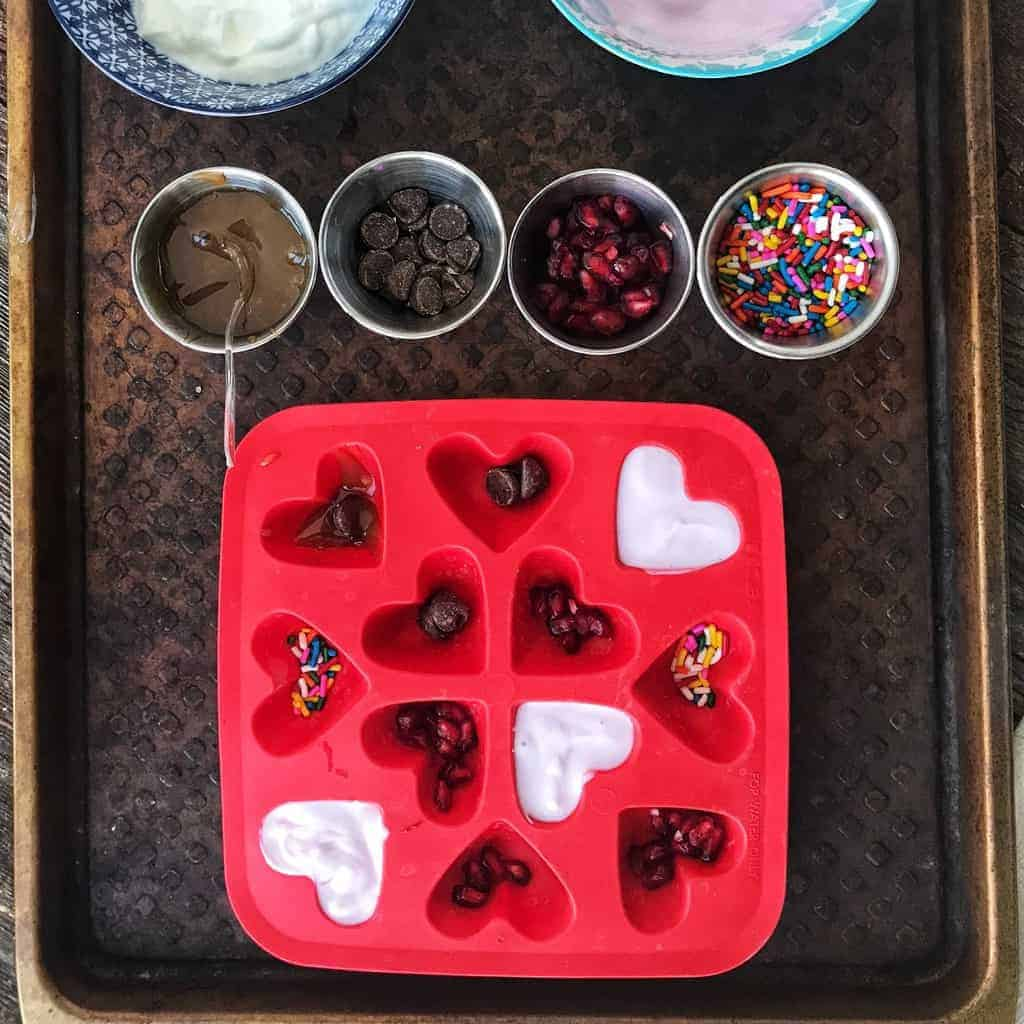 A red heart mold with pomegranate seeds, sprinkles, and chocolate chips in the molds, some molds have yogurt on top.
