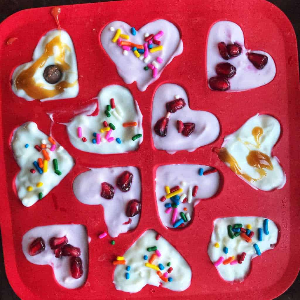 A red heart mold with vanilla and cherry yogurt in it with sprinkles, pomegranate seeds, and caramel sauce on different molds.