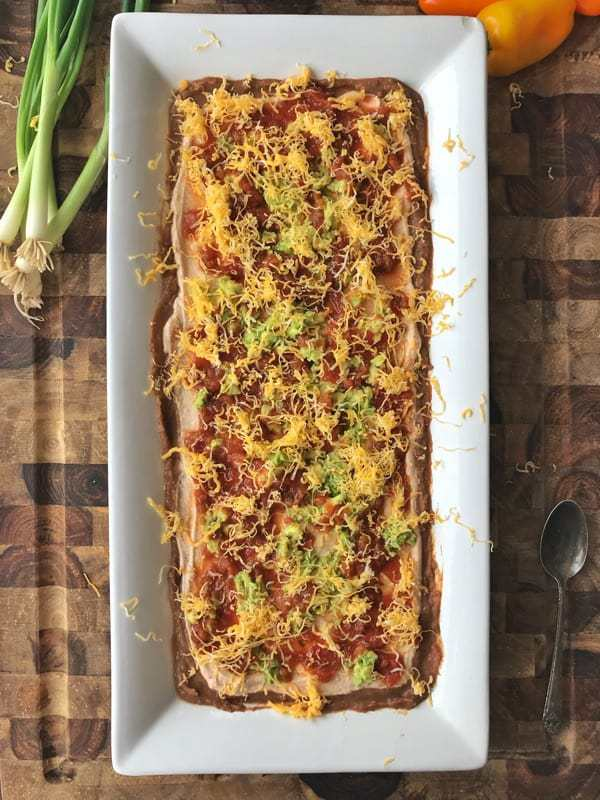 Refried bean dip recipe shown with refried beans, Greek Yogurt mixture, avocado, cheese, and salsa spread on a white serving tray.