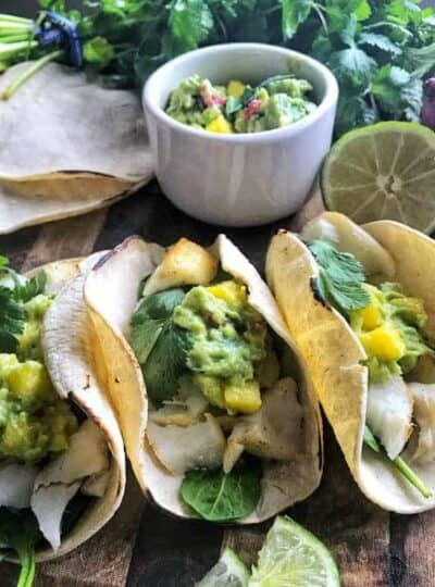 3 Baked Cod Fish Tacos with mango guacamole on top.