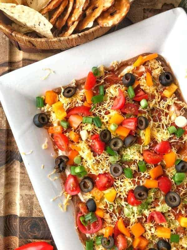 Layered Taco Dip Recipe: This healthy layered taco dip is easy to make. Using refried beans, greek yogurt, spices, salsa, and loads of veggies, its the perfect appetizer for game day or parties. Enjoy with tortilla chips, pretzel chips or even veggie sticks.