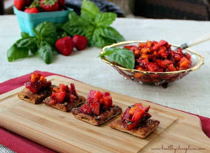 A wooden table topped with different types of food on a plate, with Strawberry and Salsa