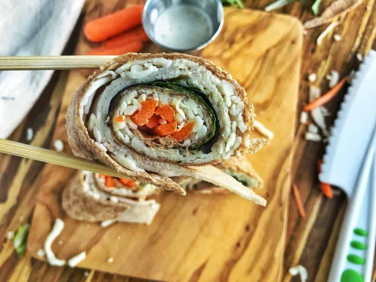 A slice of a turkey roll up is held with chopsticks. Inside is turkey, spinach, and carrots.