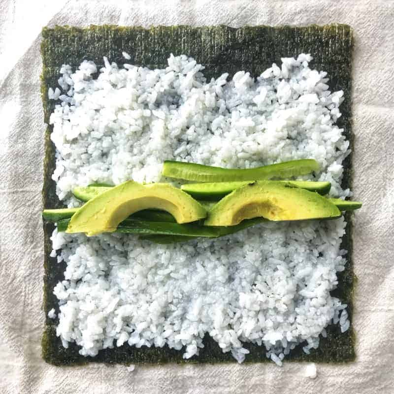 nori shown with sushi rice, avocado, and cucumber on top