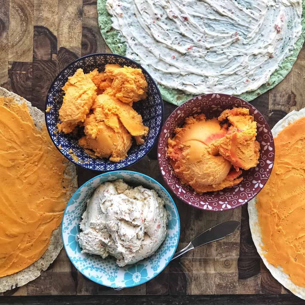 three bowls with different types of spreadable cheese are shown next to tortillas with the cheese spread on them.