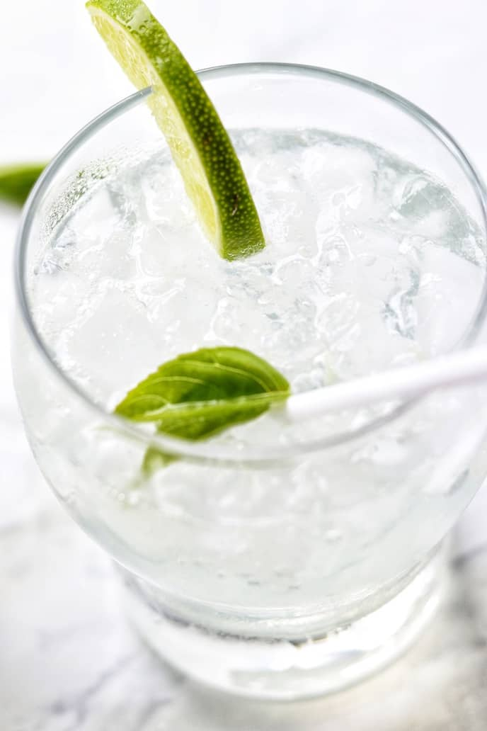Close up of a homemade soda in a clear glass with lime and a straw.