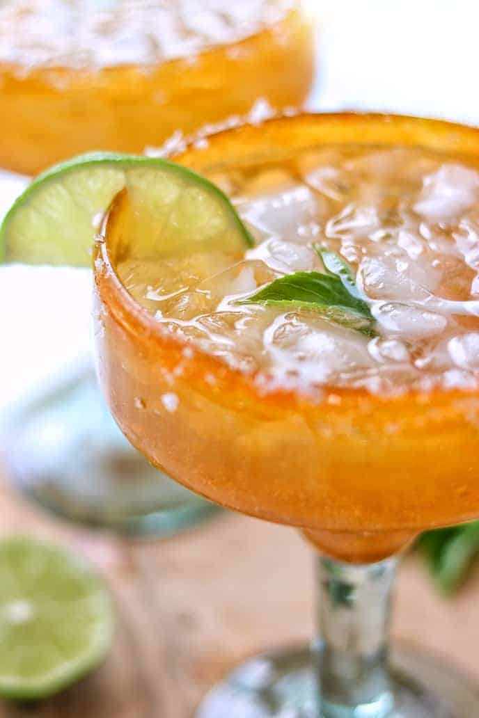 A skinny margarita recipe in an orange margarita glass filled with ice and lime on a wooden surface with a lime slice and another glass in the background