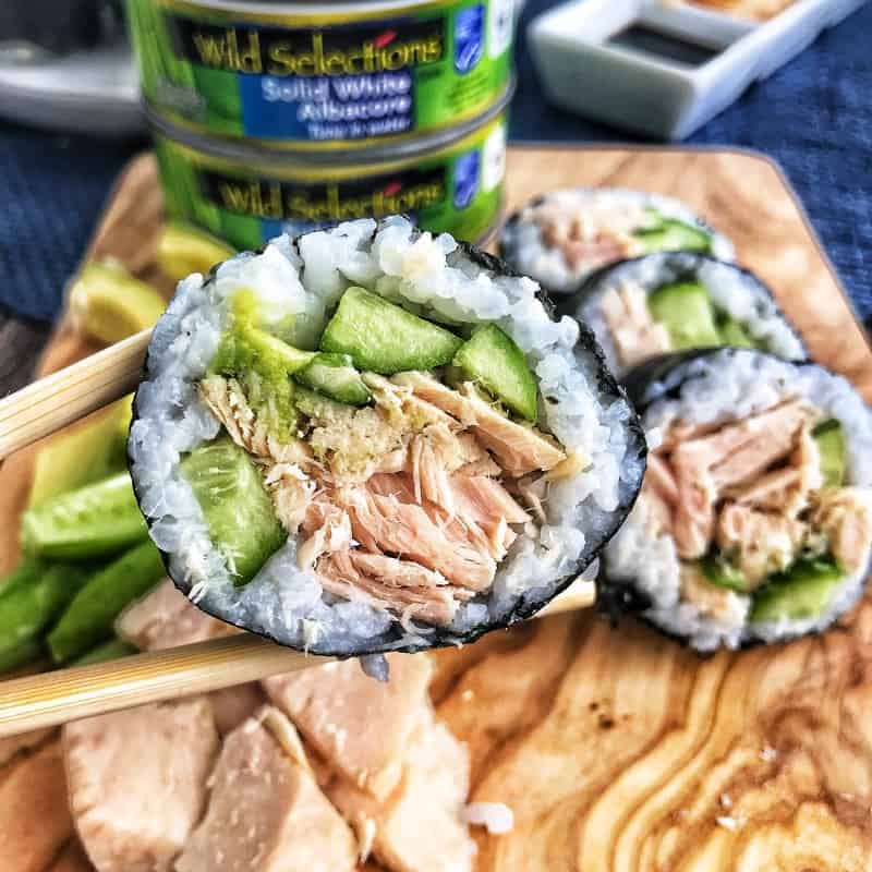 canned tuna sushi shown between chopsticks with cucumber, avocado, and rice.