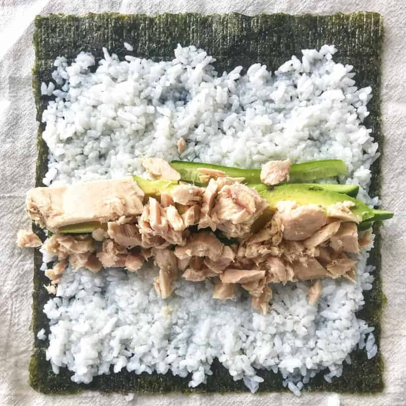nori shown with sushi rice, avocado, cucumber and canned tuna on top