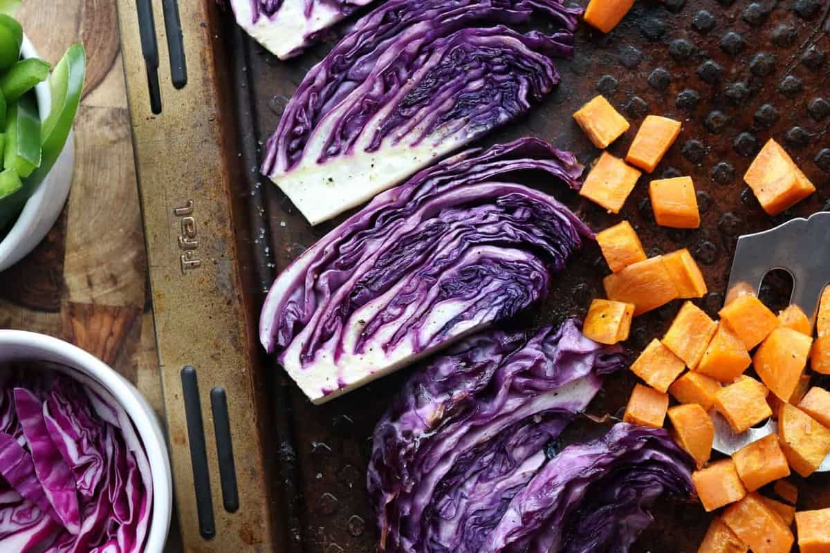 A baking sheet with red cabbage slices and sweet potato cubes.
