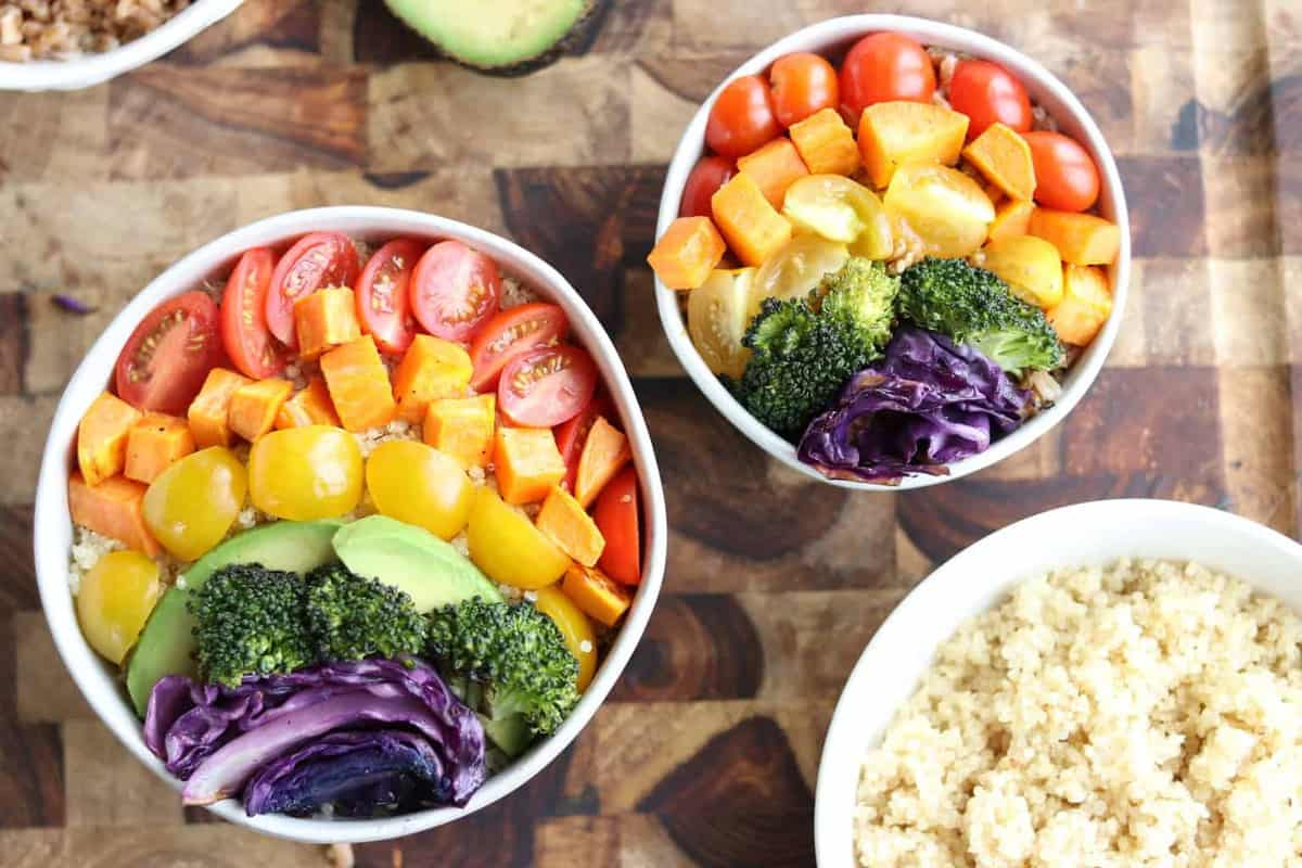 A top down view of 2 white bowls with a rainbow of veggies including tomatoes, sweet potatoes, yellow tomatoes, avocado, broccoli, and red cabbage