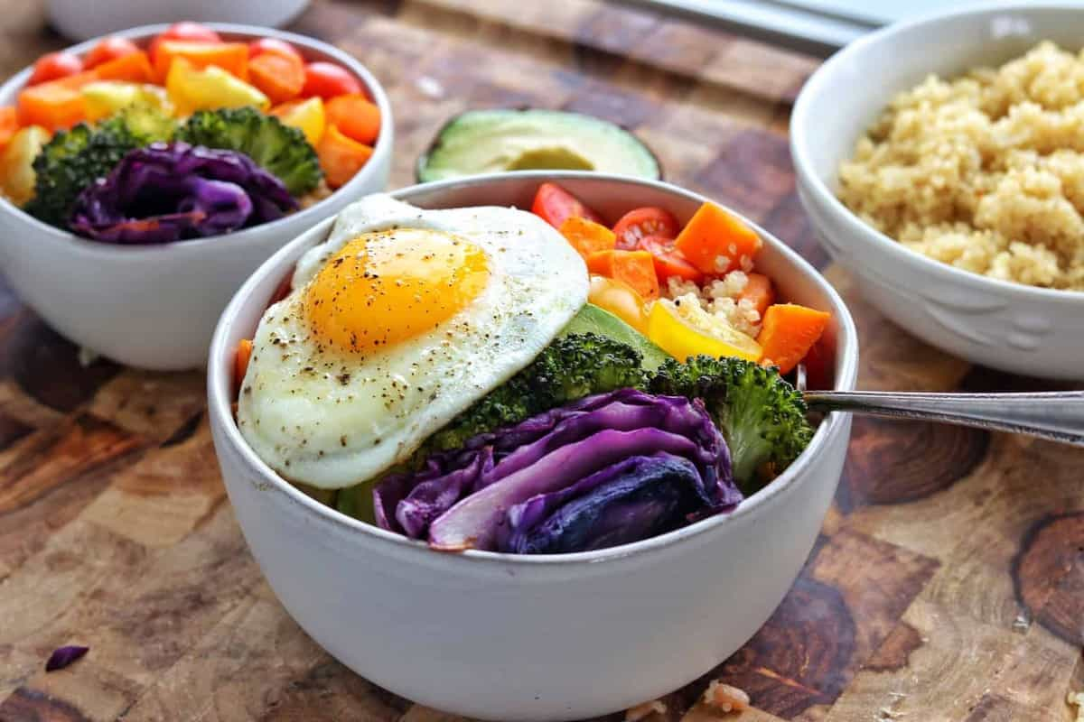 a buddha bowl with vegetables and a fried egg.