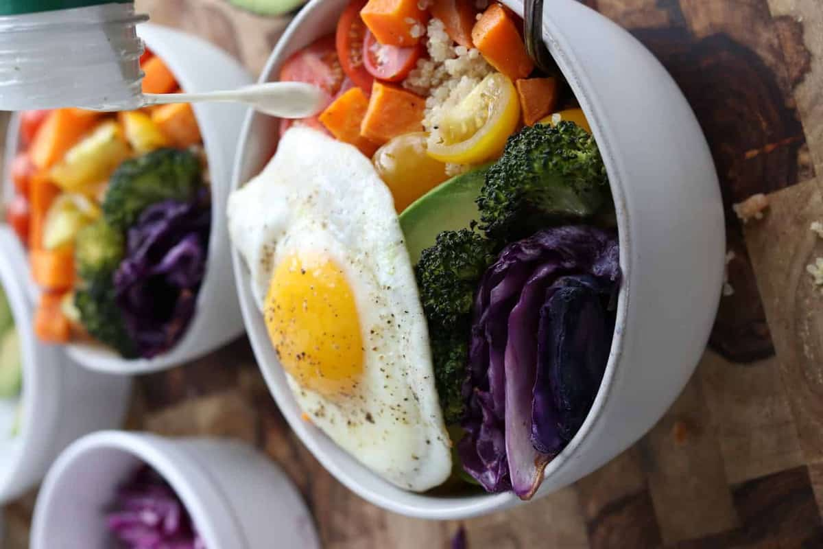 a buddha bowl with vegetables and fried egg