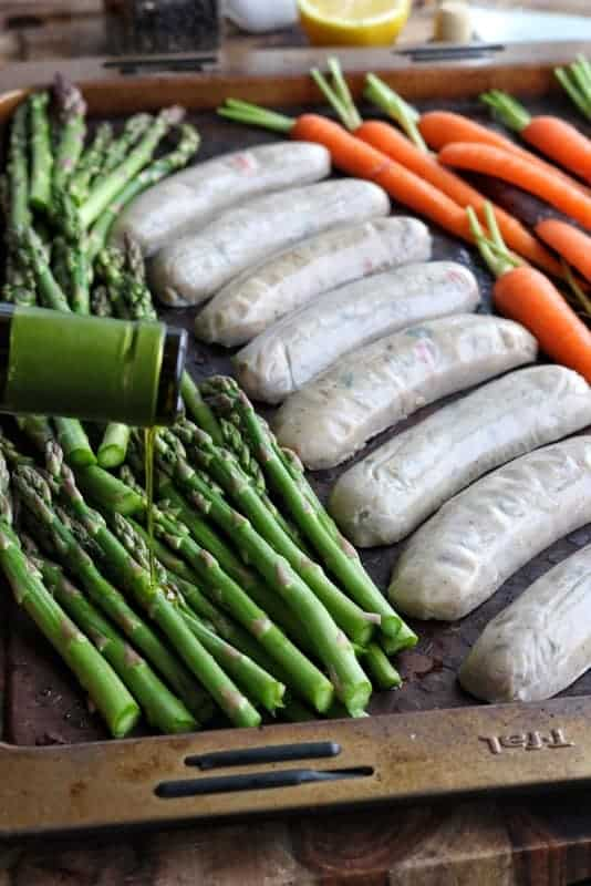 Healthy Sheet pan dinners are easy to make, this shot shows chicken sausage on a baking pan with asparagus and carrots on the sides, drizzled with olive oil.