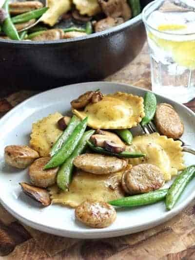 sausage ravioli with pea pods and mushrooms on a white plate.