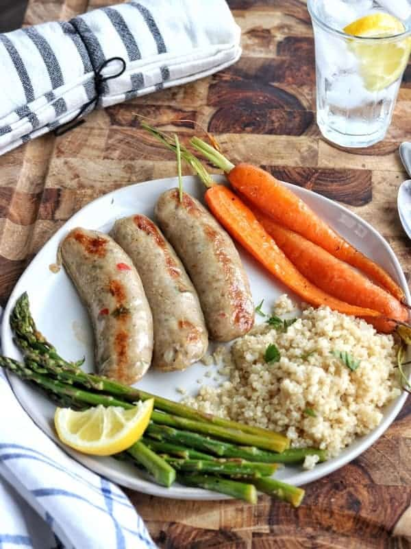 cooked turkey sausages, asparagus, carrots, and quinoa on a white plate with a lemon. A glass of ice water with lemon and dish towel in the background.