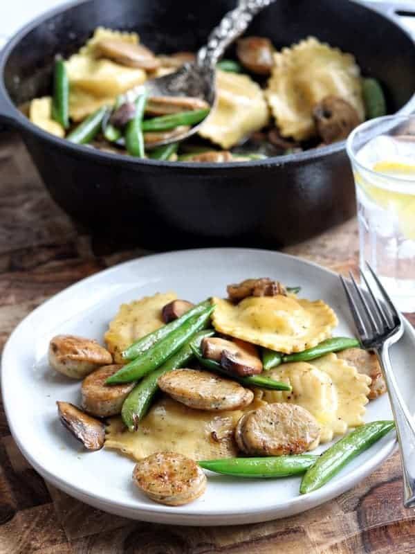 Turkey sausage, ravioli, pea pods, and mushrooms on a white plate with a fork with a cast iron pan with the same ingredients inside in the background along with a glass of ice water with lemon