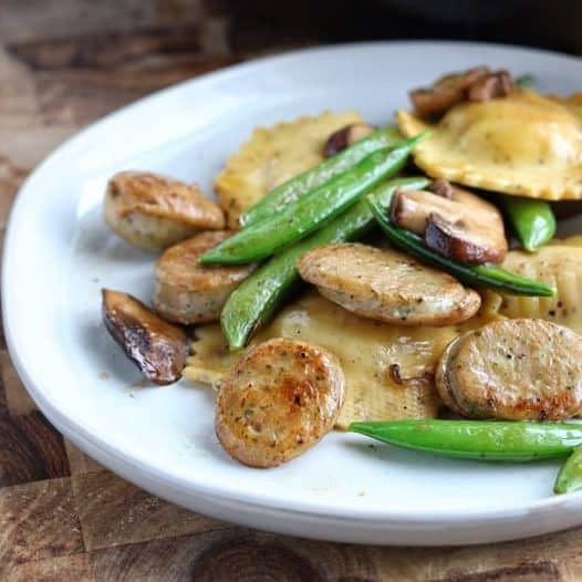 Close up shot of turkey sausage with mushrooms, pea pods and ravioli on a white plate on top of a wood surface.