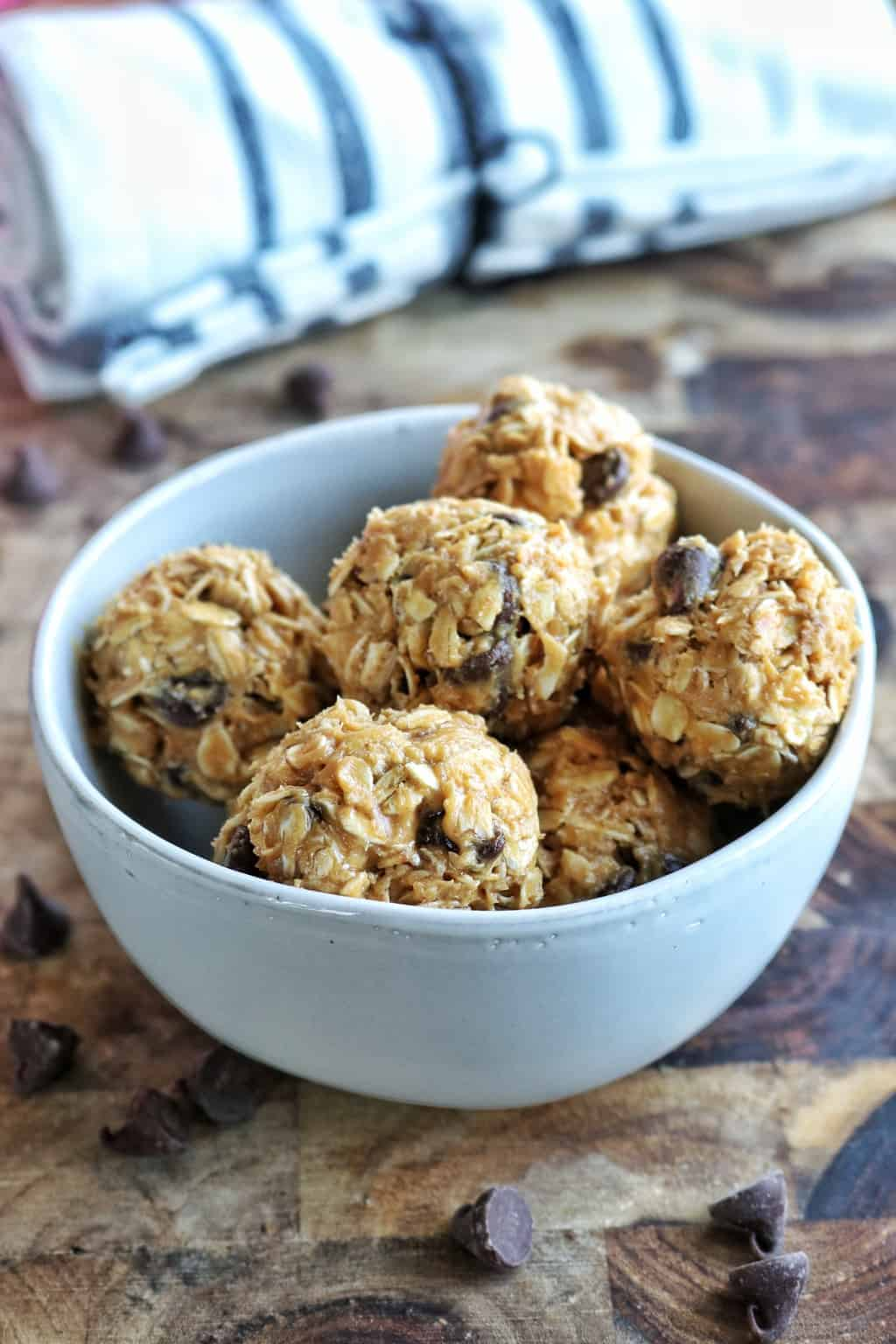 oatmeal peanut butter balls shown stacked in a white bowl on a wood surface with chocolate chips around it.