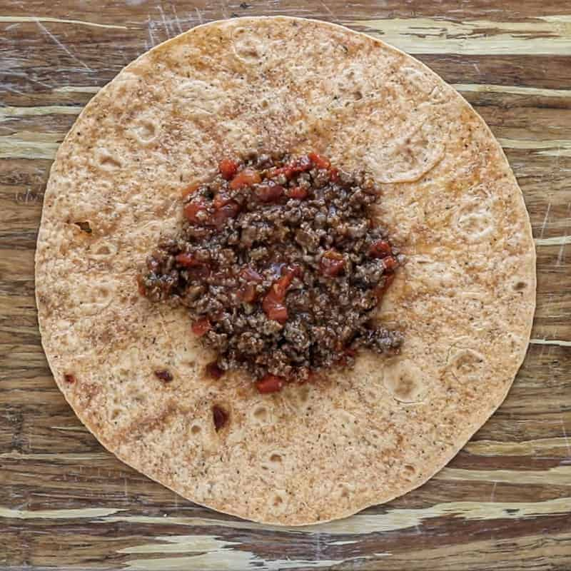 Crunchwrap supreme being made on a large flour tortilla with ground beef in the middle.