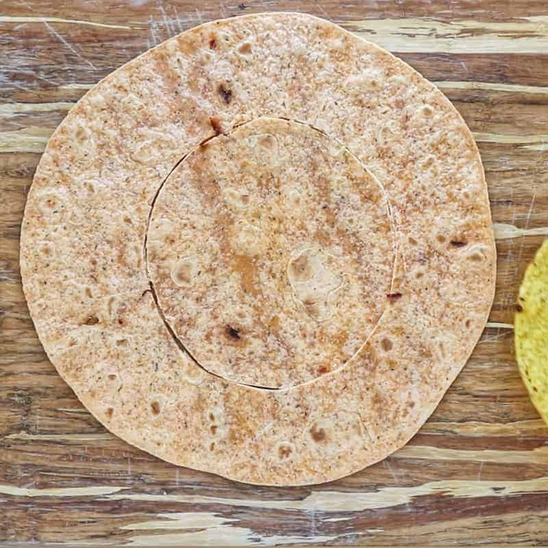 Crunch Wrap Supreme Recipe showing a large flour tortilla traced with a knife to cut out a circle in the tortilla.