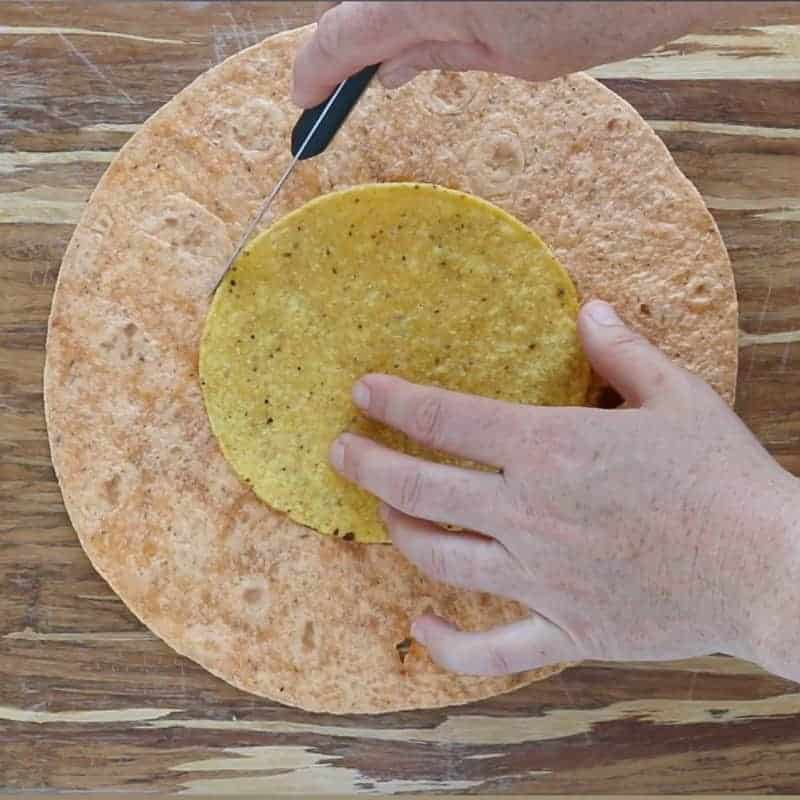Crunch Wrap Supreme Recipe showing tostada on top of a large flour tortilla and being traced with a knife to cut out a circle in the tortilla.