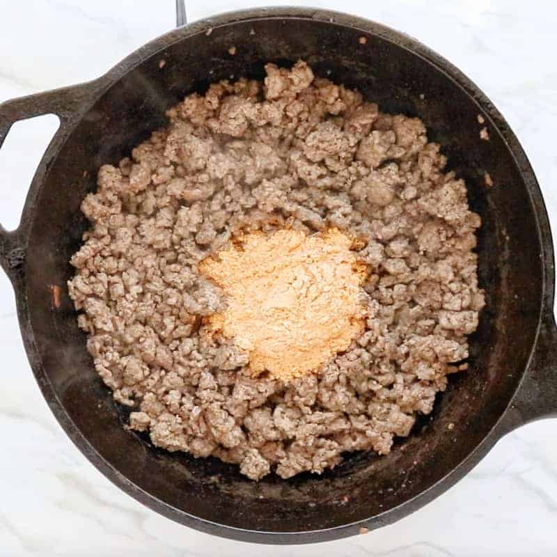 Crunch Wrap Supreme Recipe shown cooking with ground beef in a black cast iron pan with taco seasonings added.