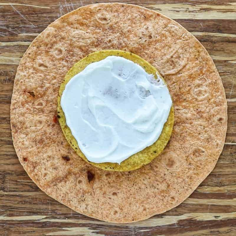 Crunchwrap supreme being made on a large flour tortilla showing a tostada with Greek Yogurt in the middle of a large tortilla.