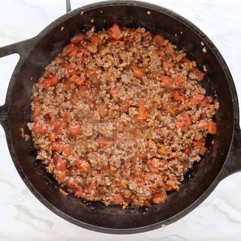 Crunch Wrap Supreme Recipe showing ground beef cooking with tomatoes in a black cast iron pan.